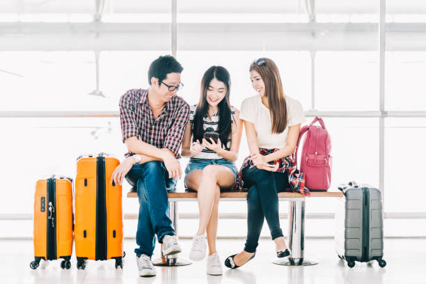 Group of young Asian travelers using smartphone checking flight or online check-in at airport together, with luggage. Travel abroad, summer holiday trip, or mobile phone application technology concept Group of young Asian travelers using smartphone checking flight or online check-in at airport together, with luggage. Travel abroad, summer holiday trip, or mobile phone application technology concept southeast asian ethnicity stock pictures, royalty-free photos & images
