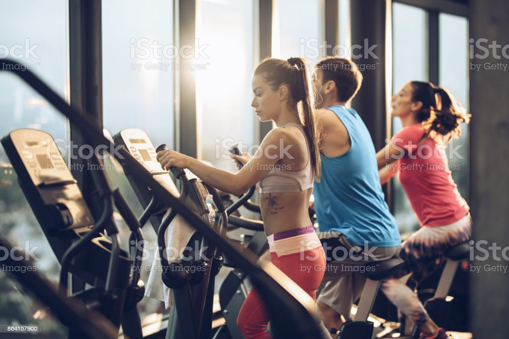 Group of young athletes exercising on sports machines in a gym. royalty-free stock photo
