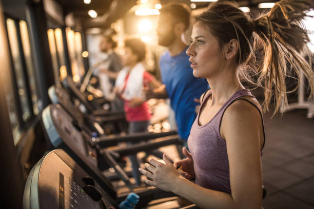 group of young athletes jogging on treadmills in a gym. - treadmill stock photos and pictures