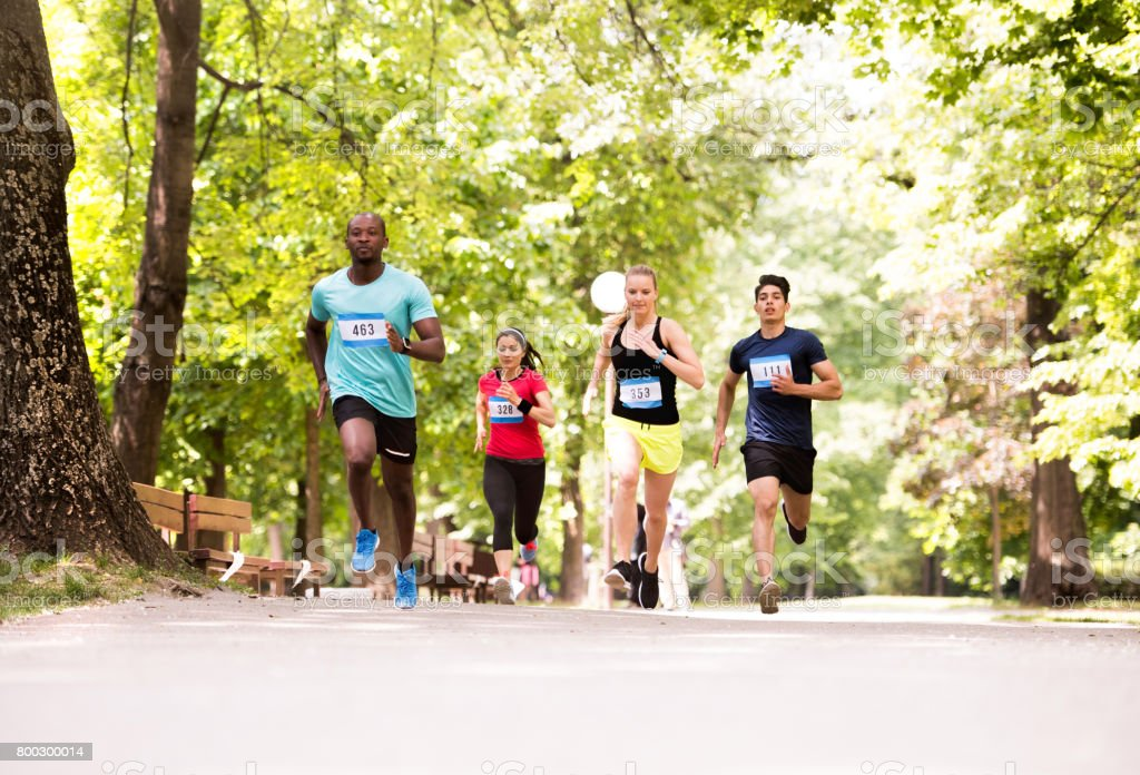 Group of young athletes running in green sunny park. stock photo