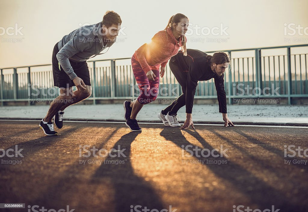Group of young athletes starting a race at sunset. stock photo
