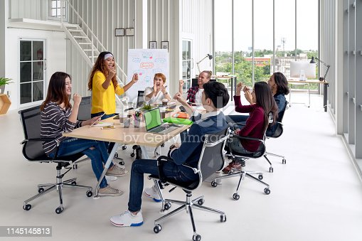 istock Group of young attractive asian creative design team meeting at office celebrating success or winner. Asian employee engaged together with effective and productive meeting and happy workplace concept. 1145145813