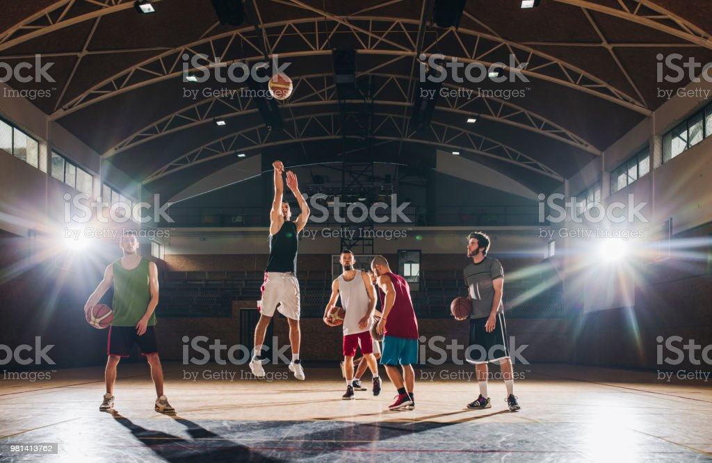 Full length of basketball team exercising with balls on a sports...