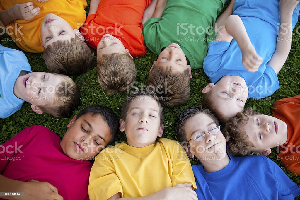 group of young boys relaxing and sleeping in the grass stock photo