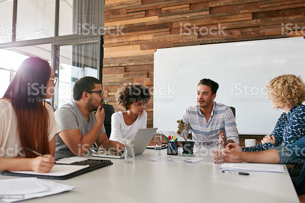 Group of young business professionals having a meeting stock photo
