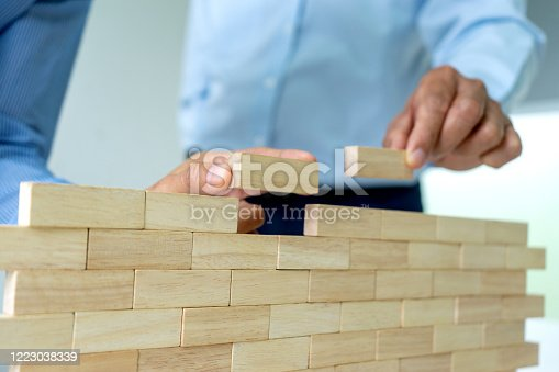 group of  Young businessman try to build wall and tower from wooden brick block go to top of a tower