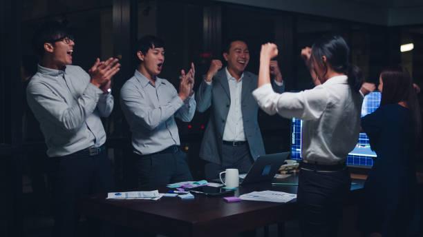 若いビジネスマンのグループアジアの実業家とビジネスウーマンは、夜間オフィスの会議室で契約または契約を扱い、署名した後、5を与えることを祝います。 - public ストックフォトと画像