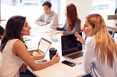 Group Of Young Businesswomen Sitting Around Table In Modern Workspace Having Working Lunch Meeting
