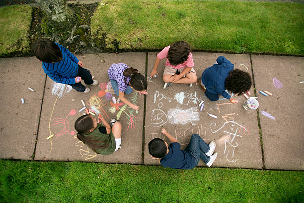 Group of young children drawing with chalk on the sidewalk Group of young children making art on the sidewalk chalk art equipment stock pictures, royalty-free photos & images