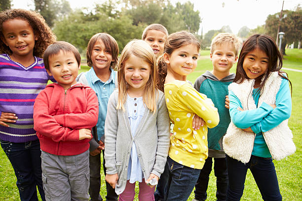 Group Of Young Children Hanging Out In Park stock photo