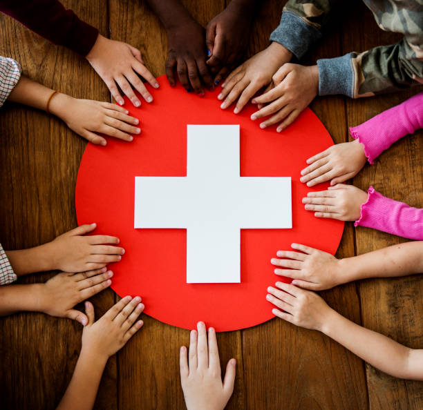 a group of young children learning about first aid - first aid stock photos and pictures