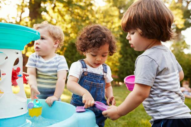 gruppe von kindern spielen mit wasser-tisch im garten - 2 3 jahre stock-fotos und bilder