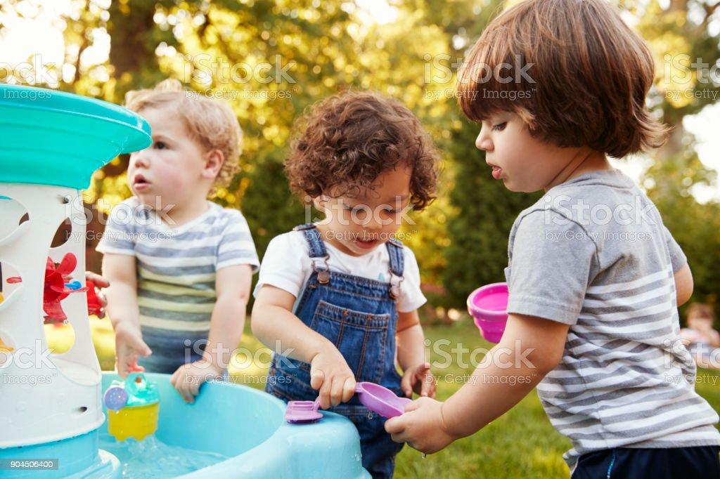Grupo de niños jugando con agua de mesa en jardín - foto de stock