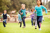 Group Of Young Children Running Towards Camera In Park Smiling To Camera