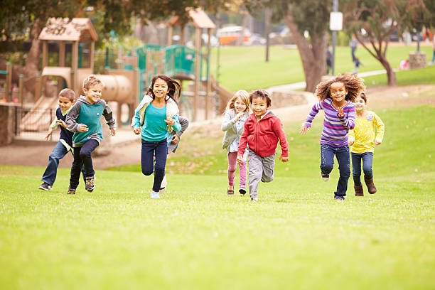 group of young children running towards camera in park - oyun alanı stok fotoğraflar ve resimler
