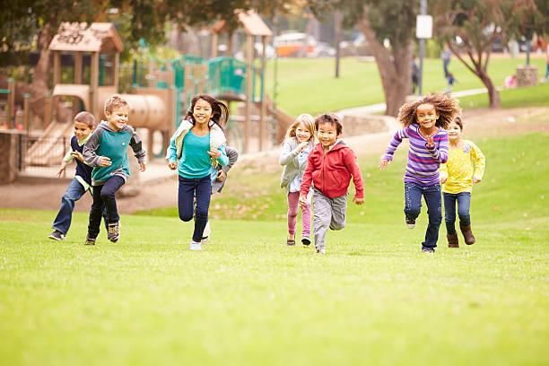 group of young children running towards camera in park - speeltuin stockfoto's en -beelden