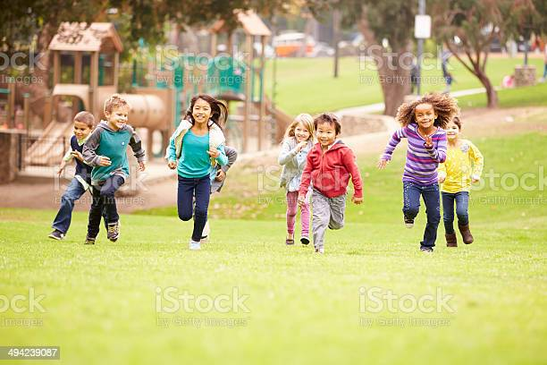 Group Of Young Children Running Towards Camera In Park Stock Photo - Download Image Now