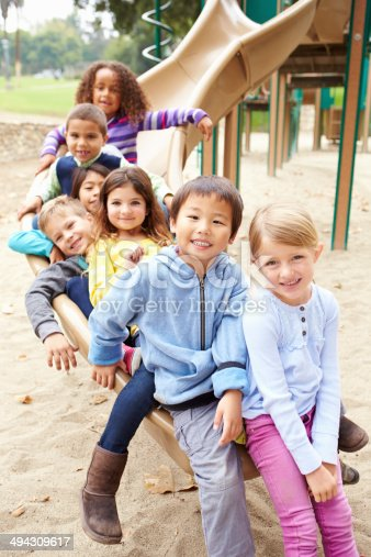istock Group Of Young Children Sitting On Slide In Playground 494309617