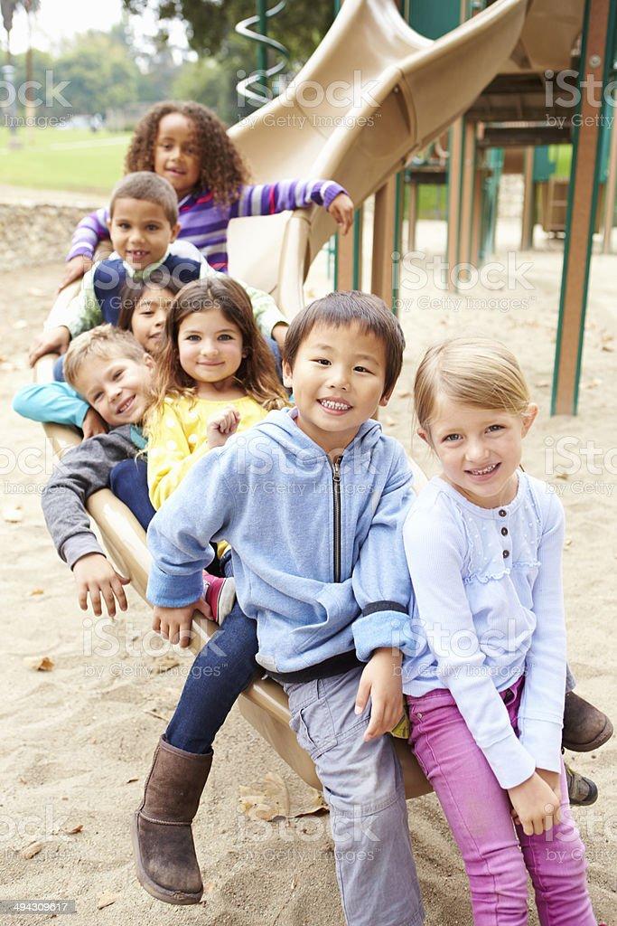 Group Of Young Children Sitting On Slide In Playground stock photo