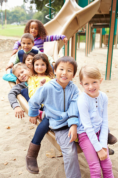 group of young children sitting on slide in playground - sliding stock photos and pictures