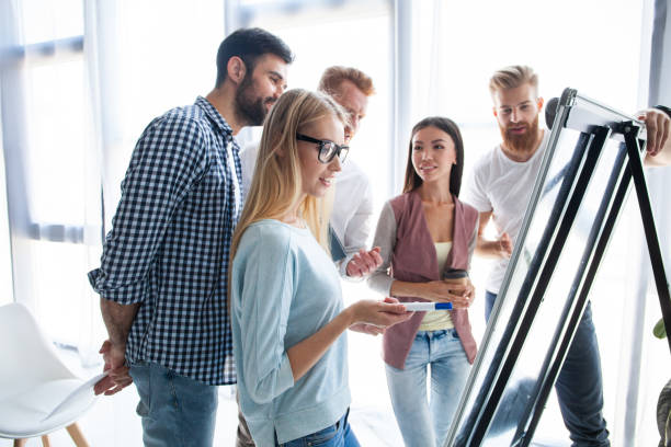 Group of young colleagues dressed casual standing together in modern office and brainstorming. Group of young colleagues dressed casual standing together in modern office and brainstorming flipchart stock pictures, royalty-free photos & images