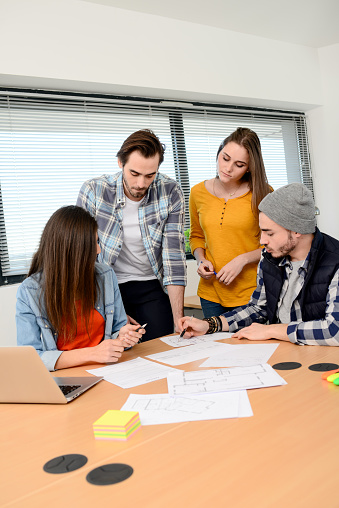 918746260 istock photo group of young cool hipster business people in casual wear working together in meeting room of a startup company 653116604