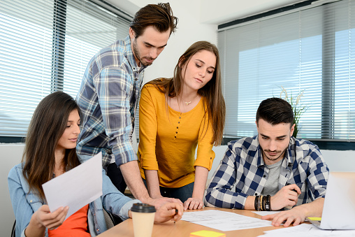 918746260 istock photo group of young cool hipster business people in casual wear working together in meeting room of a startup company 653116614