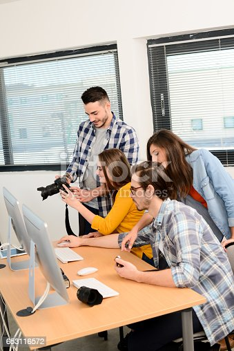 918746260istockphoto group of young cool hipster creative business people in casual wear working together in a meeting room of startup company looking at photography on computer 653116572