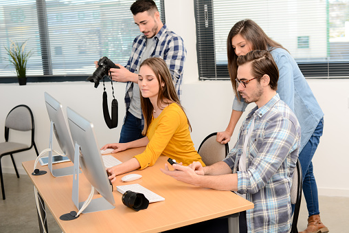 918746260 istock photo group of young cool hipster creative business people in casual wear working together in a meeting room of startup company looking at photography on computer 653116584