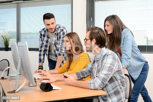 918746260istockphoto group of young cool hipster creative business people in casual wear working together in a meeting room of startup company looking at photography on computer 653116632
