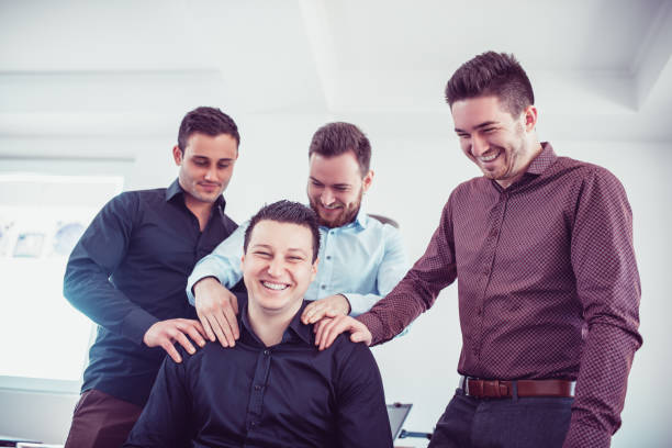 Group of Young Coworkers Making Fun of Colleague in Office stock photo