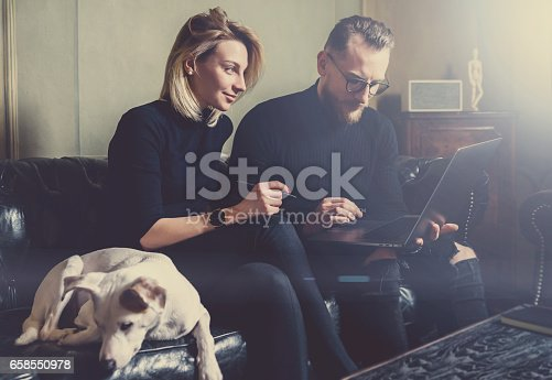 istock Group of young coworkers making great business decisions.People discussing new project at modern meeting room.Man using laptop, woman smiling, white dog sleeping on sofa. Visual effects, flare. 658550978