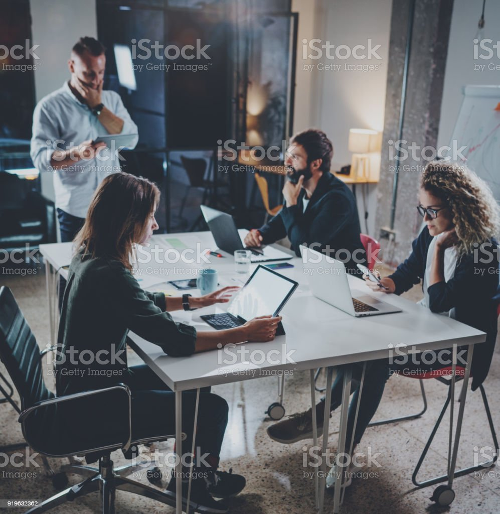 Group of young coworkers work together modern coworking studio.Young people making conversation with partners at the table.Horizontal.Blurred background.Square. stock photo