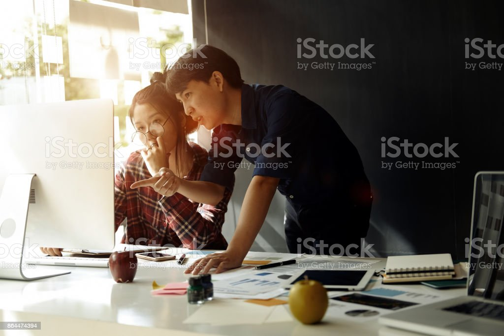 Group of young coworkers working together in modern office.Woman talking with colleague about new startup project. stock photo