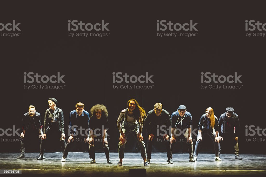 Group of young dancers on the stage Group of young performers on the stage standing in the line. Dark tones. 20-29 Years Stock Photo
