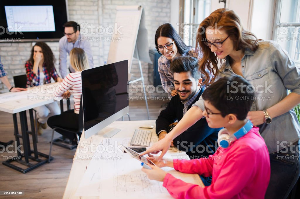 Group of young designers looking at digital tablet royalty-free stock photo