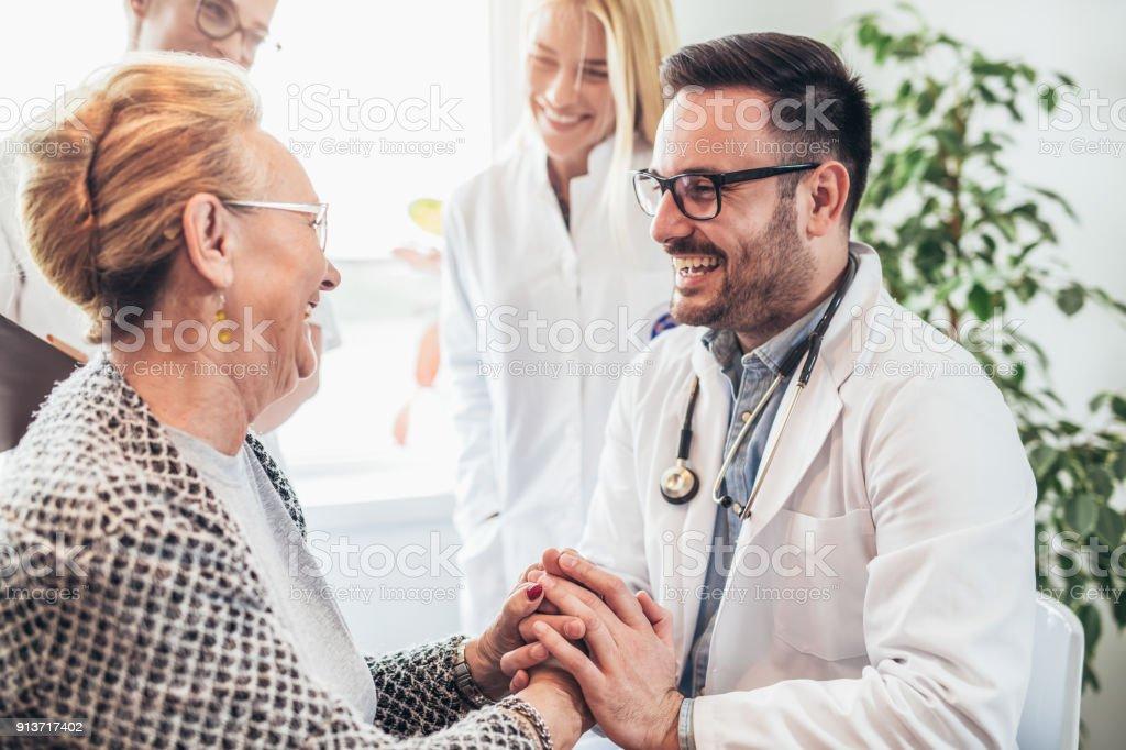 Grupo de joven médico durante la visita a domicilio personas mayores - foto de stock
