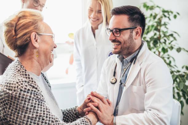 groep van jonge arts tijdens huis bezoek senior mensen - raam bezoek stockfoto's en -beelden