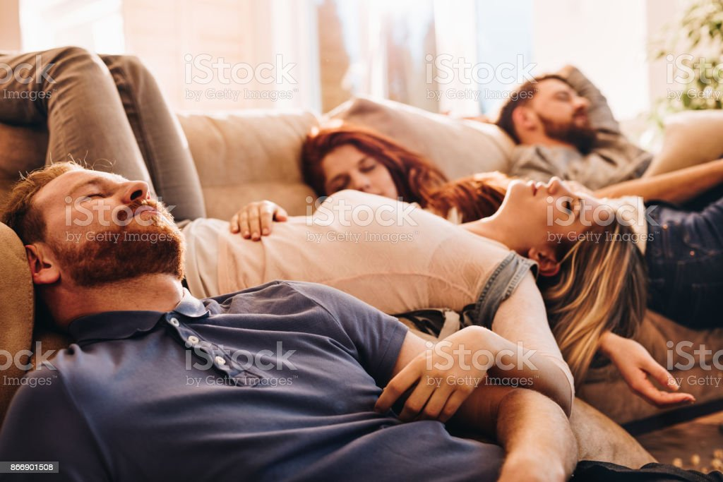 Group of young drunk people sleeping in the living room. stock photo