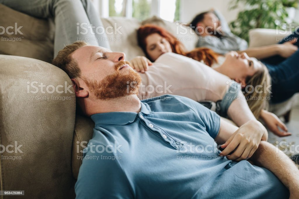group of young drunk people sleeping in the living room stock photo