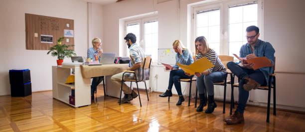 groep jonge ingenieurs is zorgvuldig op zoek via de nieuwe taken die zij hebben gekregen terwijl een van hen is praten met de mooie vrouwelijke baas op haar bureau. - netherlands map stockfoto's en -beelden