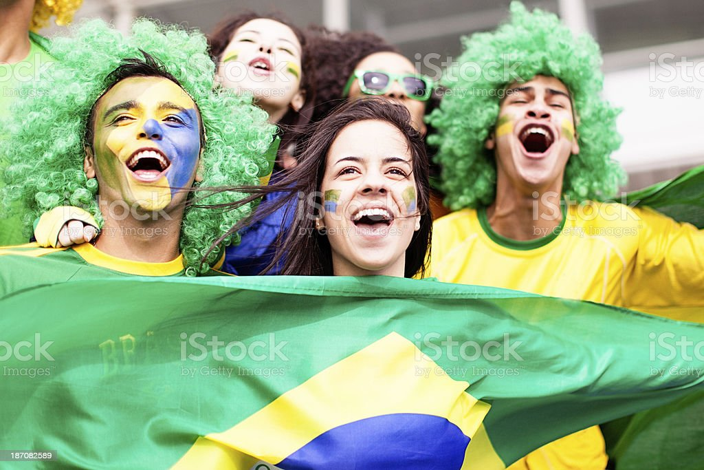 A group of young fans cheering for Brazil at football match stock photo