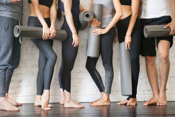 group of young fitness people. legs close up view - metodo pilates foto e immagini stock