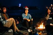 夜にビーチでクリスマスを祝う若い友人のグループ