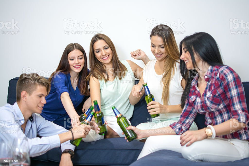 Group of young friends cheering with bear bottles. stock photo