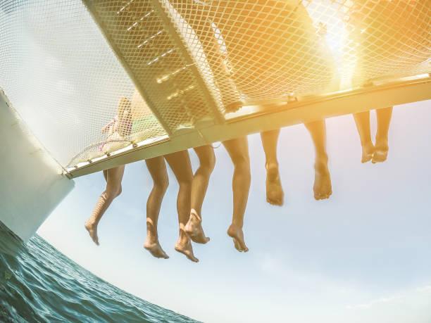 grupp unga vänner kylning i katamaran båt - avslappnad människor att göra tur ocean resa - resor, wanderlust, sommar, vänskap, ungdom, tropiska koncept - fokus på två vänster män fötter - retro filter - katamaran bildbanksfoton och bilder