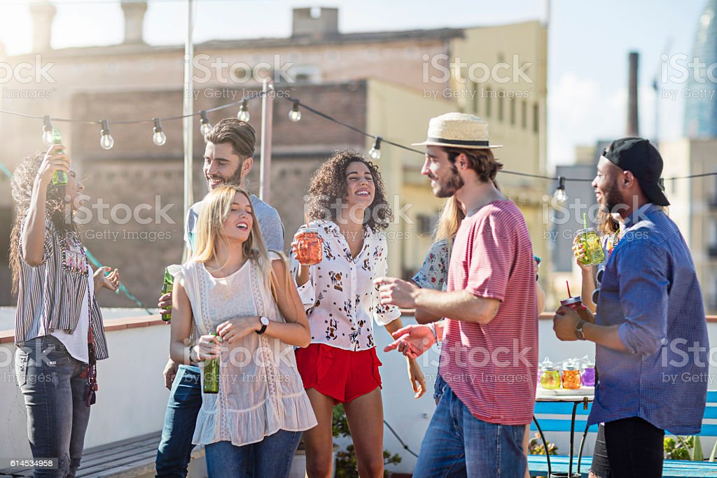 Group of young friends dancing at rooftop party stock photo