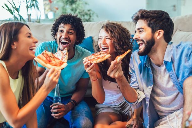 Group of young friends eating pizza.Home party.Fast food concept. stock photo