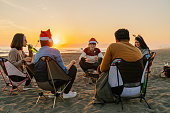 ビーチでクリスマスパーティーを楽しんだり、マシュマロを食べたりする若い友達のグループ