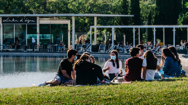 Lisbon, Portugal - June 6, 2020: Group of young friends follow the rules of social distancing a nd masks in a park in Lisbon, Portugal stock photo